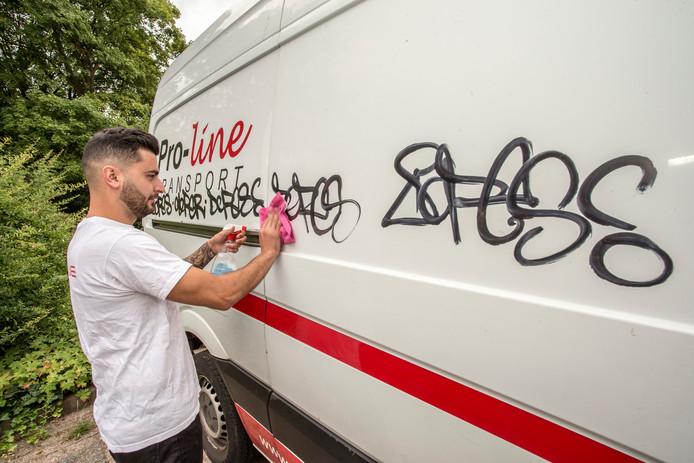 Ondernemer Stephan Towmasjan probeert zijn door een graffitispuiter 'getagde' bedrijfsbus schoon te krijgen. Hij gaat woensdag aangifte doen.