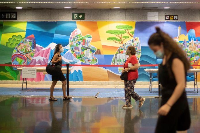 Reizigers in een metrostation in Barcelona.  De muur achter de reizigers laat een eerbetoon zien aan de hulpverleners die druk zijn met de gevolgen van het coronavirus.