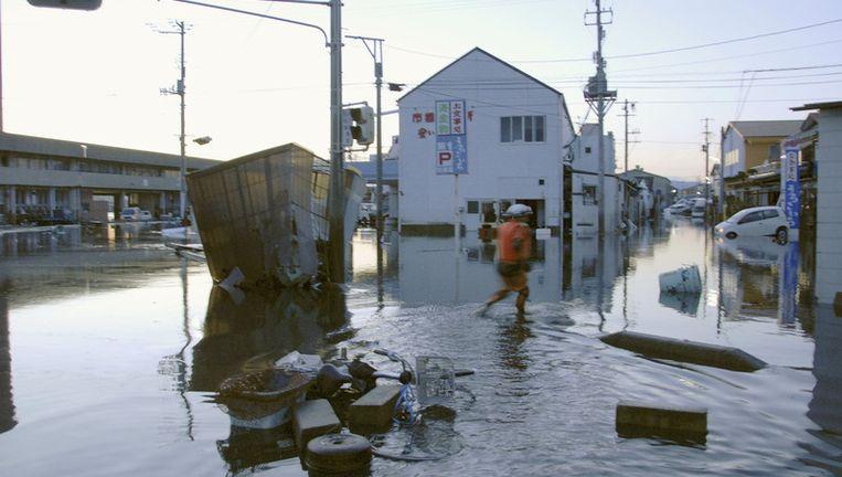 Een man waadt door een ondergelopen straat in Japan. Beeld ap