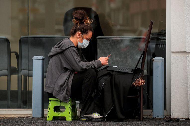 Een vrouw in New York werkt op de parkeerplaats van een bedrijf dat wegens het coronavirus gesloten is.   Beeld REUTERS