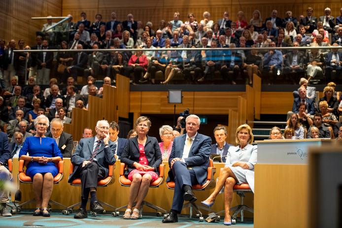 Andries Heidema met links naast hem zijn vrouw en ouders luistert naar toespraken voor zijn installatie als commissaris van de Koning.