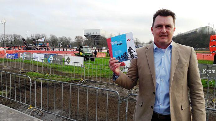 De Bredase wethouder Paul de Beer toont het Wielerplan West-Brabant zaterdag op het parkoers van de Cyclocross in Rucphen. Op de achtergrond is het Skidome te zien.