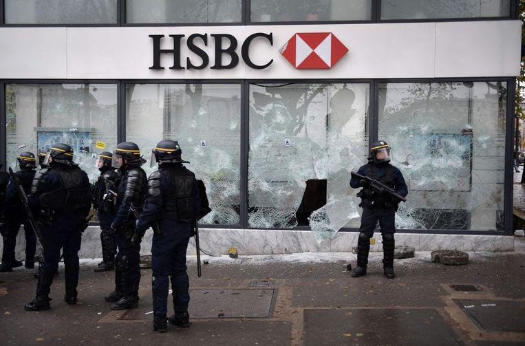 Oproerpolitie bij een kantoor van de bank HSBC waar de ramen werden ingeslagen.