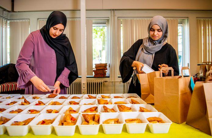 Twee van de vier meiden bereiden maaltijden voor.