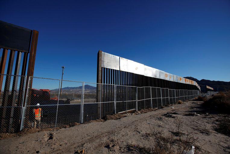 Een arbeider langs een nieuw gebouwd stuk van de grens tussen de VS en Mexico.