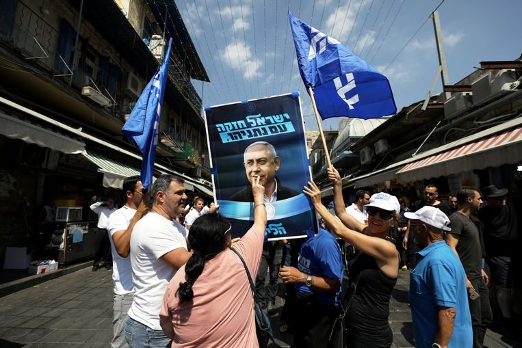 Supporters van Benjamin Netanyahu houden een verkiezingsposter van de langstzittende premier omhoog op de markt van Jeruzalem.  Beeld Ammar Awad / Reuters