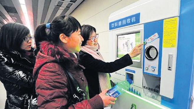 Chinese vrouwen gooien plastic flesjes in het apparaat van recyclebedrijf Incom om hun ov-kaart op te laden.
