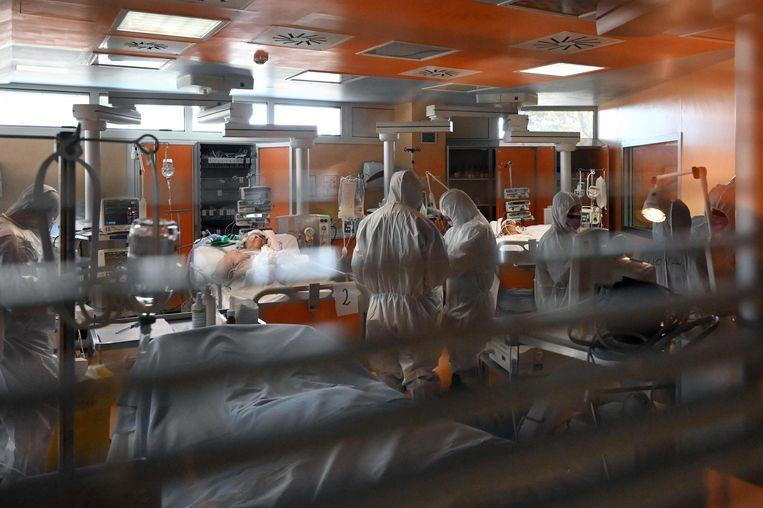 Medisch personeel in beschermende kleding behandelen patiënten besmet met het coronavirus. Beeld AFP