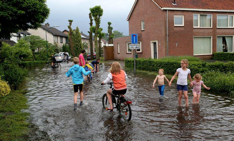 Kinderen in een ondergelopen straat in Waalre (Noord-Brabant). Beeld anp