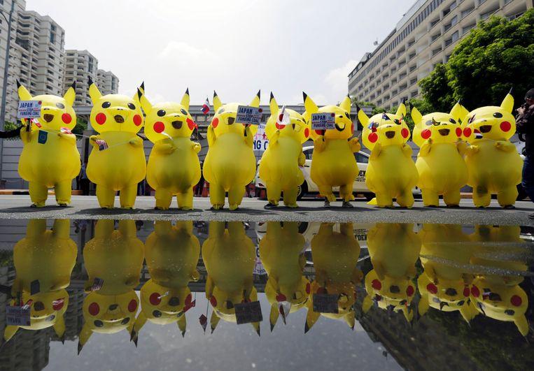 Filippijnse klimaatactivisten in Pokémon-kostuum demonstreren bij de Japanse ambassade in Manilla tegen Japanse investeringen in steenkool. Beeld EPA