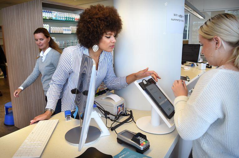 Bij Apotheek Orion in Amersfoort kunnen klanten de bijsluiter van hun medicijnen lezen met behulp van een schermpje. Het is onder meer ontwikkeld voor laag geletterden en anderstaligen. Op de foto is personeel bezig het schermpje te installeren. Beeld Marcel van den Bergh