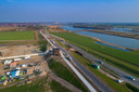 Ken je de tweede foto nog? Een luchtfoto van ruim tien jaar geleden? Die situatie is tegenwoordig helemaal anders. Er is een bypass gegraven, er zijn dijken opgespoten en de Kamperstraatweg is verlegd. Dit om onder meer ruimte te maken voor de inlaat. Dat is een brug waar bij een zeer hoge stand het water uit de IJssel in de hoogwatergeul stroomt.