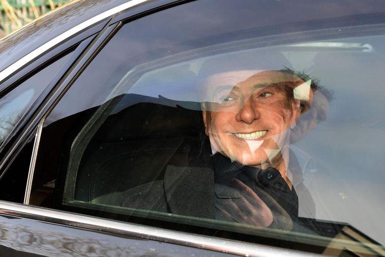 Berlusconi verlaat het stembureau na zijn stem te hebben uitgebracht. Beeld afp