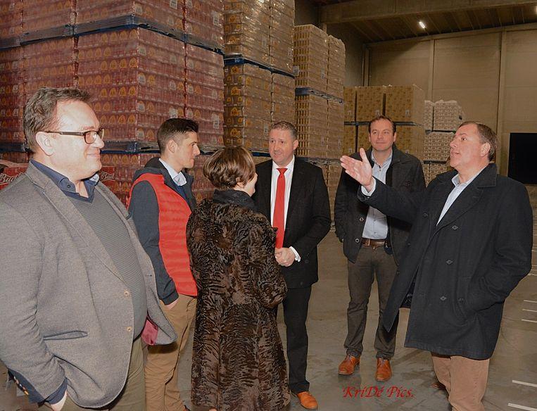 Zaakvoerder Ronny Devos omringd door de burgemeester van Poperinge en de directie van AB Inbev tijdens een bezoek aan het nieuwe magazijn.