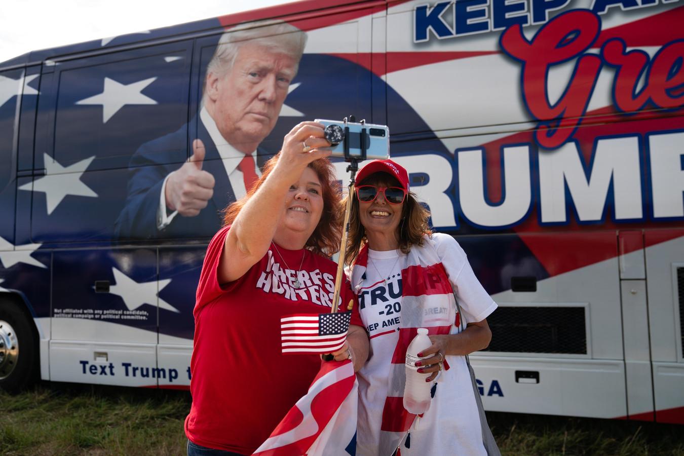 Deux femmes prennent un selfie à côté d'un bus Trump dans le parking d'un rassemblement de campagne pour le Président Donald Trump le 16 octobre 2020 à Macon, Géorgie.