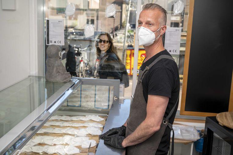 Een mondkapjeswinkel in Amsterdam krijgt veel kritiek. Er worden mondkapjes verkocht voor negen euro per stuk, waarvoor alleen contant kan worden betaald.  Beeld ANP