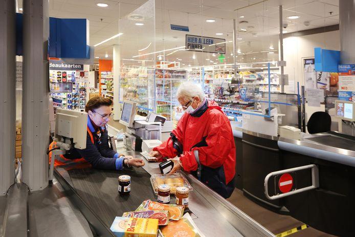 In winkelcentrum De Burcht in Breda is het rond 7.30 uur rustig. Een enkele klant beweegt zich langs de schappen van Albert Heijn. Caren Claus (73) zegt bij de kassa blij te zijn met het speciale openingsuur voor ouderen.