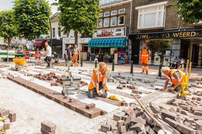 De stratenmakers zijn bezig met het aanleggen van een zebrapad op de Slotlaan in Zeist.
