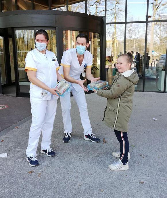 Cato overhandigt de koekjes aan de ingang van het ziekenhuis.
