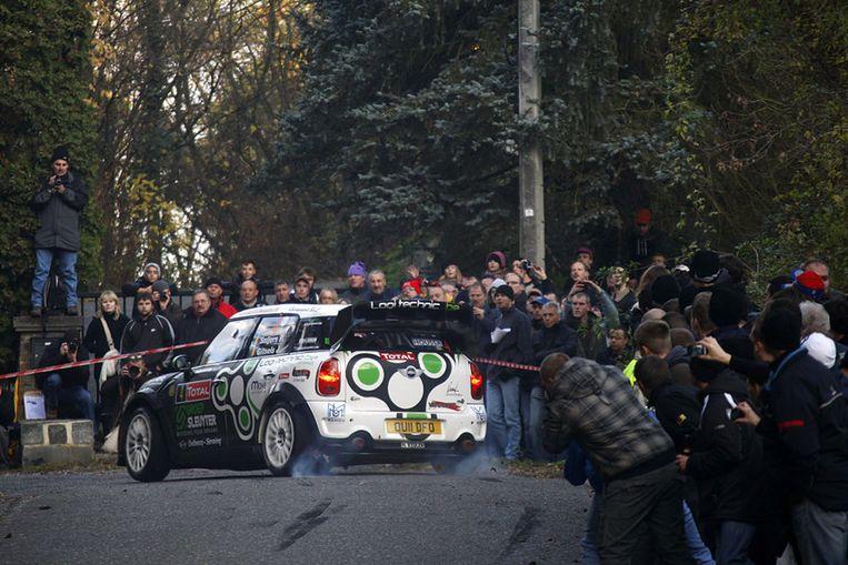 De Belgische rallyrijder Patrick Snijers scheert rakelings langs het publiek tijdens de Rally van Condroz. Beeld afp