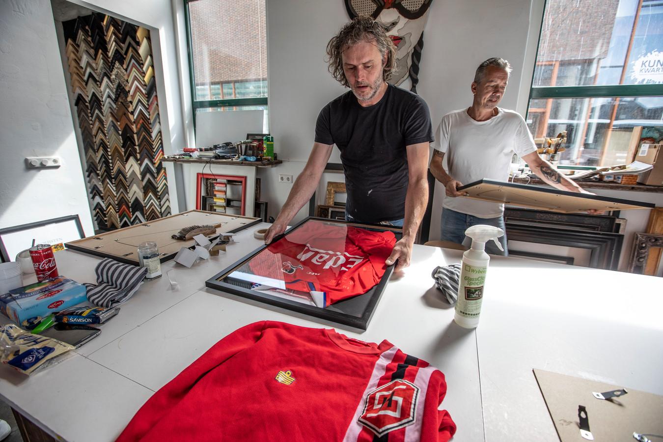 Roel Hanssen (l) heeft weer een historisch Helmond Sport-shirt ingelijst. Hij krijgt hulp van Alec Christiaens. Op de voorgrond het shirt van Ad de Wert uit de jaren 70.