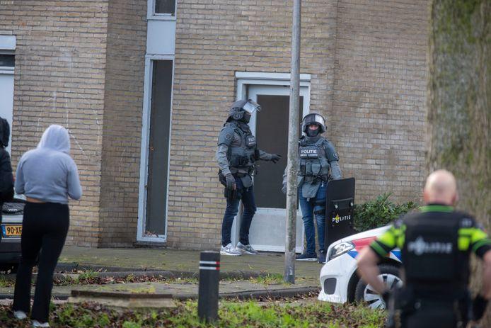 Agenten in beschermende kleding bij de ingang van de woning.