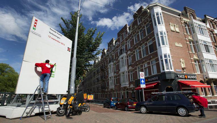 Een verkiezingsbord wordt klaargemaakt in Amsterdam. De komende tijd gaan vrijwilligers het land in om de borden vol te plakken met partijposters. Beeld ANP