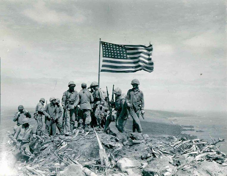 Amerikaanse mariniers hijsen de Amerikaanse vlag op de top van de berg Suribachi op het Japans eiland Iwo Jima.