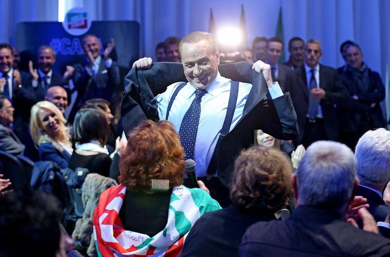 Silvio Berlusconi doet zijn jas uit om zijn borstspieren te laten zien.  Beeld EPA