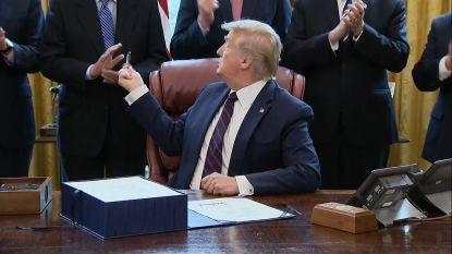 Trump deelt pennen uit na het ondertekenen van noodwet