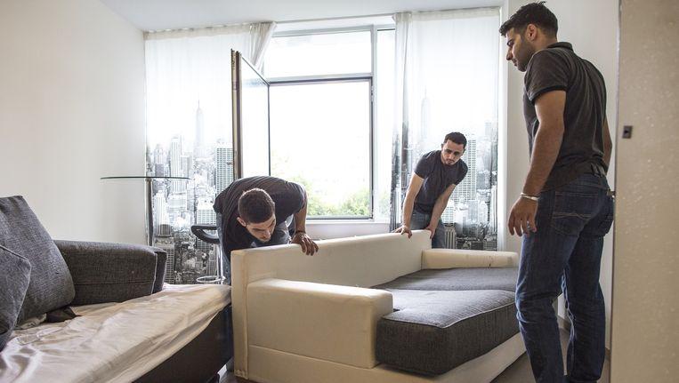 Drie Syrische vluchtelingen richten hun kamer in in het voormalige GAK-gebouw in Amsterdam-West Beeld Marc Driessen