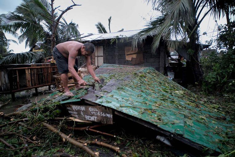 Een man herstelt het dak van zijn ingestorte huis na doortocht van tyfoon Kammuri op de Filipijnen.