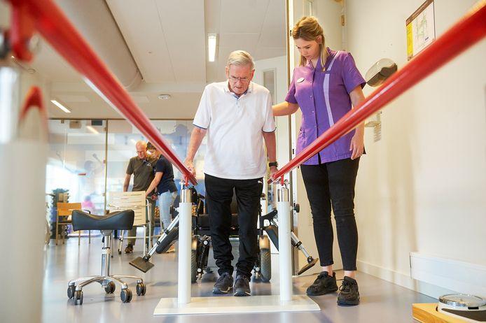 Verpleegkundige Marloes Claassen begeleidt Han Zwanenberg op de loopband.
