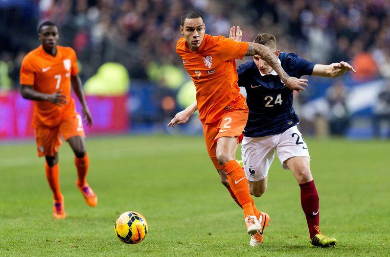 Gregory van der Wiel (M) in duel met Lucas Digne (R) van Frankrijk tijdens een vriendschappelijke oefeninterland in het Stade de France. Beeld anp
