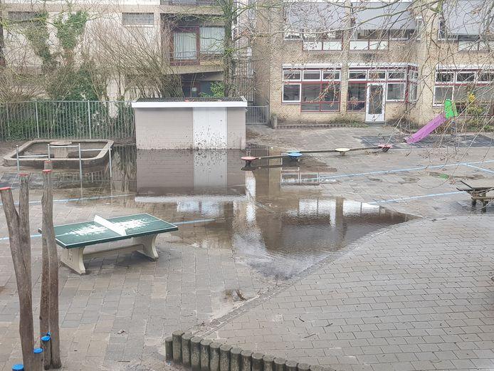 Ook op het schoolplein van basisschool de Avonturijn in De Pijp ligt een regenplas.
