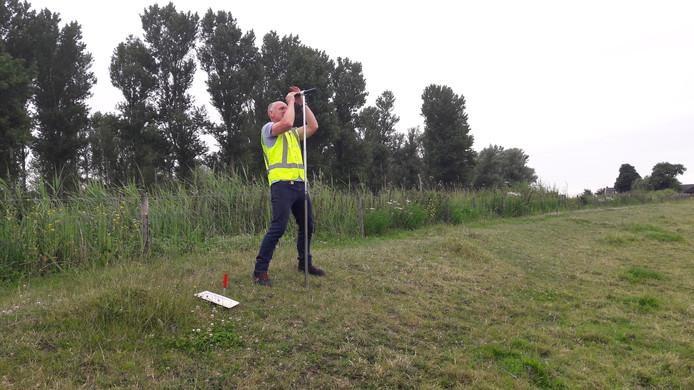 Johan Kolk van het Hoogheemraadschap van Rijnland inspecteert de dijk met een grondboor.