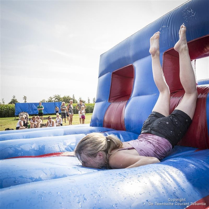 Deelneemster aan de Weide Games bij de Zomerfeesten in De Pollen-West Geesteren komt met moeite over een obstakel.