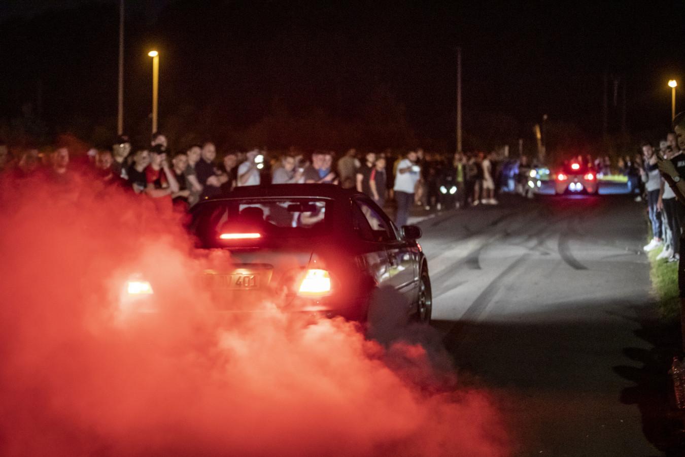 De hoofdroute op de parkeerplaats van IJsbaan Twente verandert in een racebaan. Het publiek staat schouder aan schouder aan weerszijden van het asfalt, om de drifters aan te moedigen.