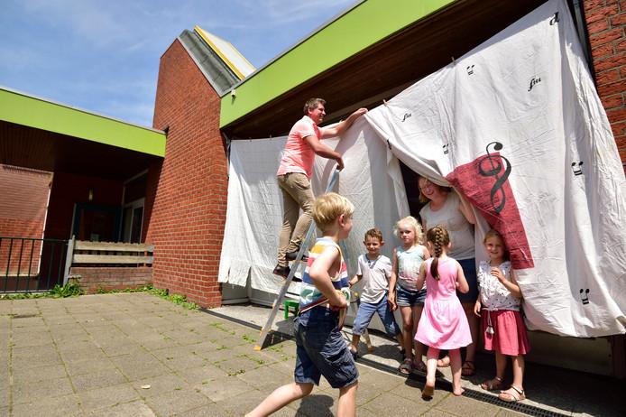 Directeur Richard Joosse en juf Mieke van Engelen hangen witte lakens voor de ramen om ervoor te zorgen dat leerlingen en leekrachten van De Carrousel in Gouda het koel houden in de klas.
