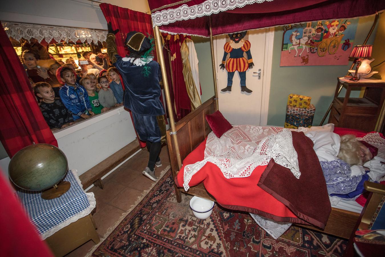Sinterklaas ligt nog te slapen. Piet is er wel klaar mee en opent alvast de gordijnen.