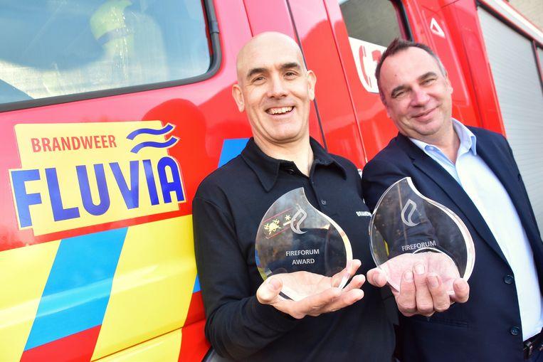 Zonecommandant Frank Maertens (links) en Francis Benoit, voorzitter van de hulpverleningszone Fluvia, tonen trots enkele de Fire Forum Awards die recent werden uitgereikt, onder meer voor het droneproject bij Fluvia.