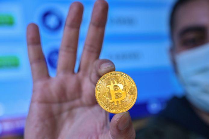 Een man houdt een bitcoinmunt vast. Een imitatie natuurlijk, want het is een digitale munteenheid.