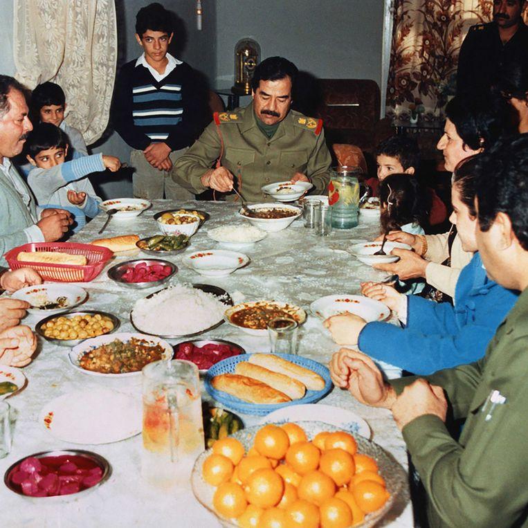 Saddam Hoessein prikt een vorkje mee bij een familie in Basra. Het is 1986, Irak is in oorlog met Iran.