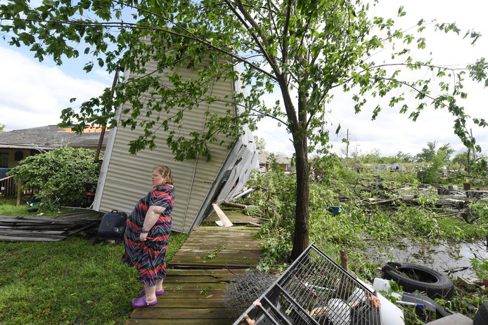 Een vrouw staat bij haar verwoeste huis.