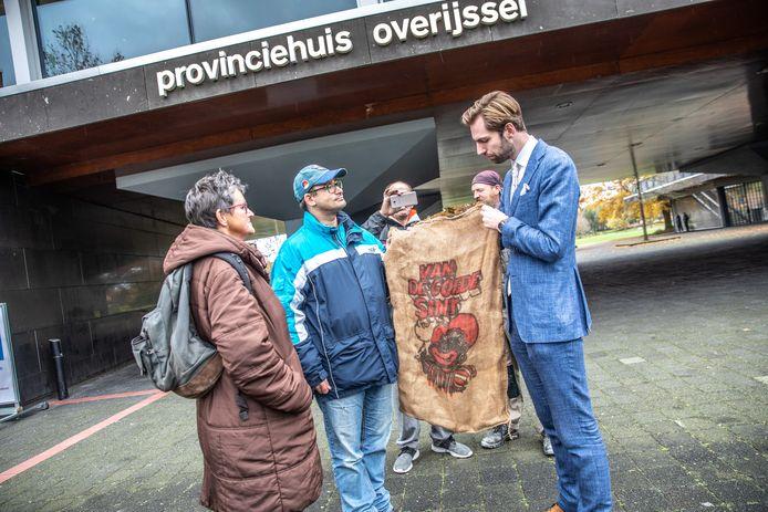 Voorstanders van zwarte piet overhandigen Joeri Pool van PVV Overijssel een jute zak.