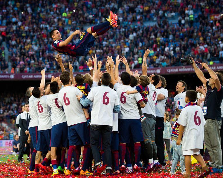 Xavi wordt bedankt door zijn teamgenoten. Coach Enrique kijkt lachend toe, rechts op de foto. Beeld Getty Images