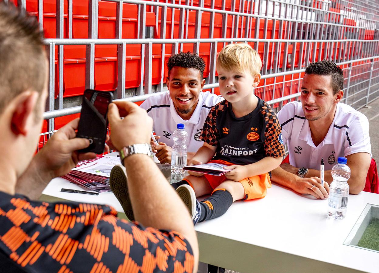 Donyell Malen en Nick Viergever gaan met een jonge supporter van PSV op de foto.
