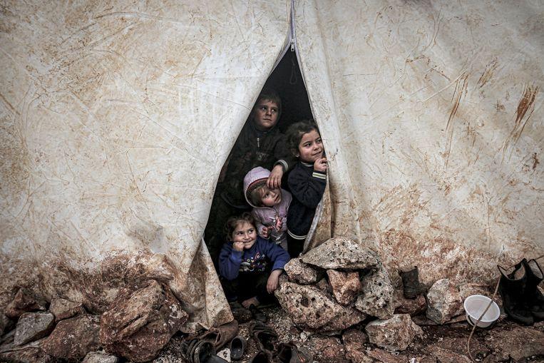 Syrische kinderen kijken door de opening van een tent in Idlib. Beeld Anadolu Agency via Getty Images
