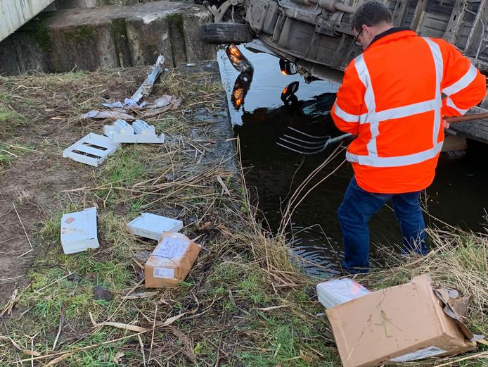 Met een riek worden de pakketjes uit water gevist na het ongeval in Heeswijk-Dinther.