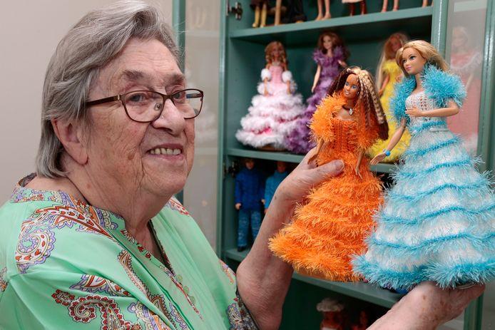 Josien toont enkele van de kleurrijke creaties waarmee ze barbies aankleedt.